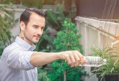 Mężczyzna nawadniał drzewa zasadzał w jego podwórku zdjęcie royalty free