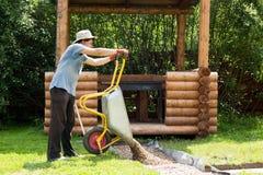 Mężczyzna niesie żwir dla ścieżek w wheelbarrow obrazy royalty free
