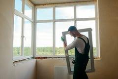 Mężczyzna niesie okno fotografia stock