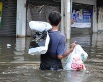 Mężczyzna niesie posiadania w zalewającej ulicie Bangkok z powrotem, Tajlandia, na 06 2011 Listopadzie Obrazy Stock