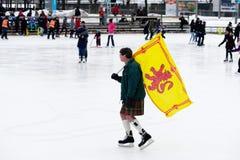 Mężczyzna niesie Szkockiego chorągwianego łyżwiarstwo w Montreal zdjęcia royalty free