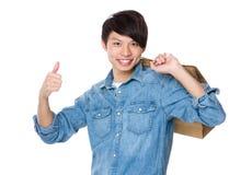 Mężczyzna niesie z torba na zakupy up i kciukiem Fotografia Stock