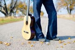 Mężczyzna nogi w cajgach z gitarą opróżniają wiejską drogę Zdjęcia Stock