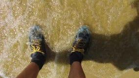 Mężczyzna nogi w sneakers Mężczyzna stoi na seashore piaska fala mokrych sneakers podróżnym odpoczynku Zdjęcie Stock