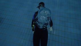 Mężczyzna nurek dmucha podwodnych bąble przy szkoleniem w nurkowej lekci w akwalung masce zbiory