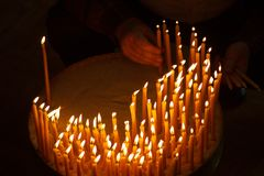 Mężczyzna oświetleniowe świeczki w kościół Zdjęcie Stock