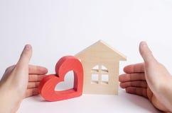 Mężczyzna obejmuje serce i dom Biznesmen tworzy wygodnego dom dla kochanków Niedrogi budynek mieszkalny dla potomstw, miłości gni zdjęcia stock