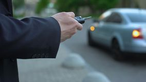 Mężczyzna obraca dalej samochodu alarm, ochrony pojęcie, ryzyko parkujący na ulicie porwanie samolotu samochód zbiory