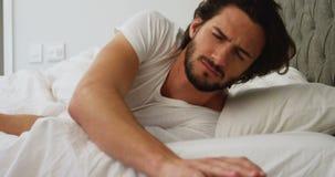 Mężczyzna obraca daleko alarm na jego telefonie komórkowym w sypialni zbiory