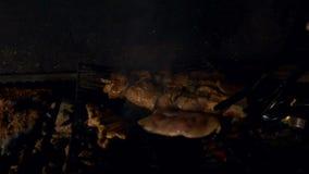 Mężczyzna obraca mięso na grillu zbiory wideo