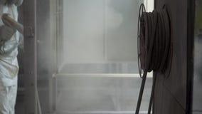 Mężczyzna obraz z kiści farby pistoletem w warsztacie klamerka Przemysłowy metalu narzut Mężczyzna w ochronnym kostiumu, jest ubr zbiory