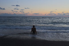 Mężczyzna obsiadanie morzem przy zmierzchem Obraz Stock