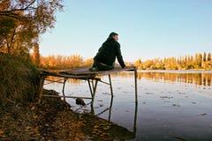 Mężczyzna obsiadanie na Drewnianym falochronie zdjęcia stock