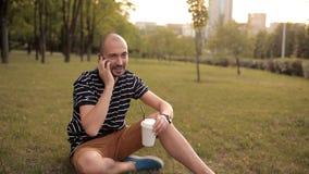 Mężczyzna obsiadanie na gazonie w zielonym parku na letnim dniu przy zmierzchem pije napój i opowiada na telefonie zbiory
