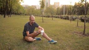 Mężczyzna obsiadanie na gazonie w zielonym parku na letnim dniu przy zmierzchem pije napój i opowiada na telefonie zbiory wideo
