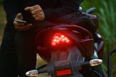 Mężczyzna obsiadanie na nowożytnej motorowej roweru zapasu fotografii Fotografia Stock