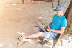Mężczyzna obsiadanie na piasku blisko drzewa i działanie na laptopie zdjęcia stock