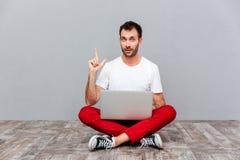 Mężczyzna obsiadanie na podłoga z laptopem i wskazywać up palcem Obrazy Stock