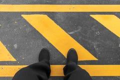 Mężczyzna obsiadanie na przemysłowej pasiastej asfaltowej podłoga z ostrzegawczym kolorem żółtym Zdjęcia Royalty Free