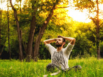 Mężczyzna obsiadanie na trawie w rozciąganiu i parku Obrazy Stock
