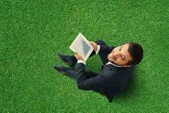 Mężczyzna obsiadanie na trawie z dotyka ochraniaczem Obrazy Royalty Free