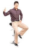 Mężczyzna obsiadanie na wysokim krześle i dawać kciuku wysoki Obraz Stock