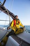 Mężczyzna obsiadanie Podczas gdy Trzymający ster jacht Przeciw niebu Obraz Royalty Free