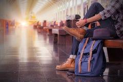 Mężczyzna obsiadanie podróży torba przy dworcem rocznika filtrowy effe zdjęcie stock