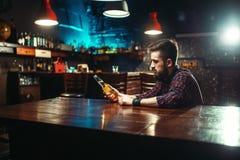 Mężczyzna obsiadanie przy prętowym kontuarem, alkoholu nałóg obrazy stock