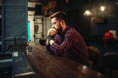Mężczyzna obsiadanie przy prętowym kontuaru i napoju alkoholem obraz royalty free