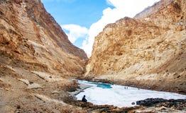 Mężczyzna obsiadanie przy rzeki stroną Zamarznięta Zanskar rzeka i Piękna góra Rzeczna spływowa krzywa fotografia stock