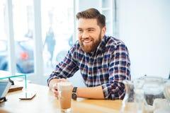 Mężczyzna obsiadanie przy stołem z cappuccino obrazy stock