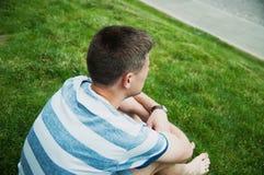 Mężczyzna obsiadanie przy trawą Obrazy Royalty Free