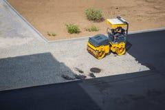 Mężczyzna obsiadanie w minitruck taranuje gruz dla dalszy instalaci asfalt na łamanej drodze obraz stock