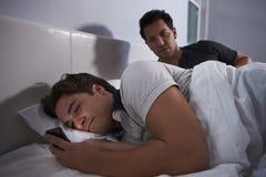 Mężczyzna obudzony w łóżku, podczas gdy jego chłopaków uses skrycie dzwonią obraz royalty free
