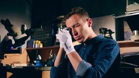 Mężczyzna ocenia pierścionek z klejnotu kamieniem przy jewellery warsztatem zbiory wideo