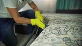 Mężczyzna od cleaning firmy angażował w czyścić kanapę Mężczyzna w jednolitym kanapy cleaning płótnie z suchym parowym cleaner zbiory