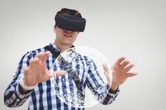 Mężczyzna oddziała wzajemnie z sferą przeciw białemu tłu w VR słuchawki Zdjęcie Royalty Free