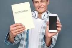 Mężczyzna odizolowywający na szarość izoluje turystyki pojęcia mienia trwanie słownika i telefon w górę ono uśmiecha się wprawiać zdjęcia royalty free