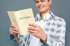 Mężczyzna odizolowywający na szarość izoluje turystyki pojęcia trwanie czytelniczego słownika szczęśliwego w górę zdjęcie stock