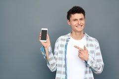 Mężczyzna odizolowywający na szarości ścianie swobodnie projektuje pozycję wskazuje przy smartphone rozochoconym zdjęcia royalty free
