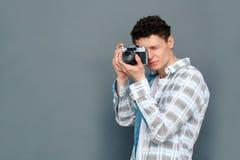 Mężczyzna odizolowywający na szarości ściany turystyki pojęcia mienia trwanie kamerze bierze obrazki koncentrujących fotografia royalty free