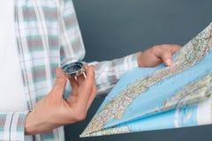 Mężczyzna odizolowywający na szarości ściany turystyki pojęcia mienia trwanie mapie patrzeje kompas w górę obrazy royalty free