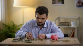 Mężczyzna odliczający pieniądze i kładzenie moneta w prosiątko banku, pieniężna piśmienność, budżet zdjęcie wideo