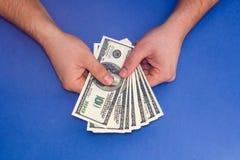 Mężczyzna odliczający pieniądze na błękitnym tle Obraz Royalty Free