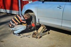 Mężczyzna odmieniania opony na samochodzie zdjęcia royalty free