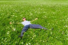 Mężczyzna odpoczynkowy lying on the beach na trawie Fotografia Stock