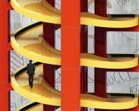 Mężczyzna odprowadzenie na niedokończonym spirala śladzie w sztaplowanie blokach zdjęcie stock