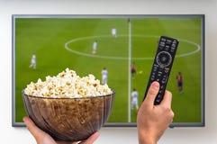 Mężczyzna ogląda futbolowego dopasowanie na TV Zdjęcia Royalty Free