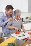 Mężczyzna ogląda jego macierzystego kucharza przy kuchnią Obraz Royalty Free